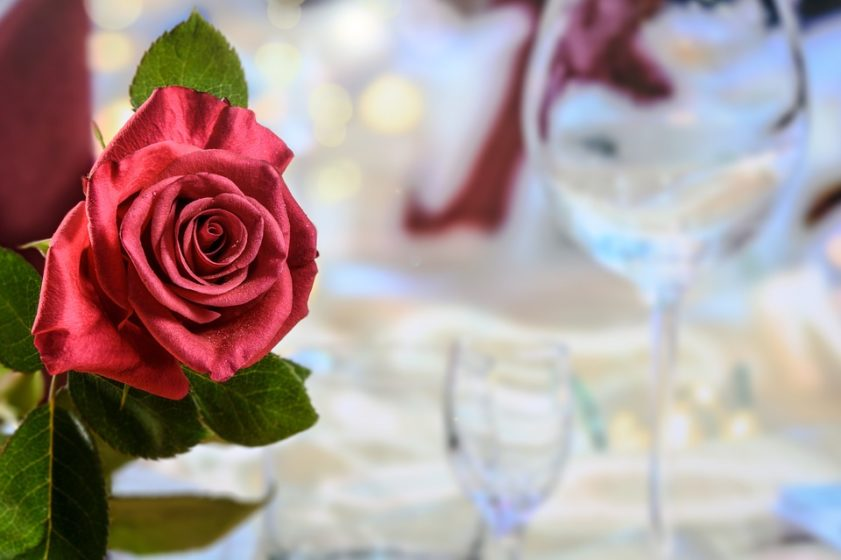 Crimson red rose at the dinner party. (Photo courtesy of https://pixabay.com/en/dinner-red-rose-love-2021656/).