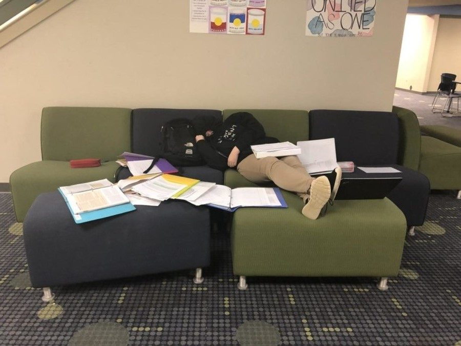Due to extreme exhaustion from staying up late to finish her homework, Anna Jernigan naps in the front commons while trying to finish the rest of her tremendous amount of work (Photo credits to Kamryn Mattison).