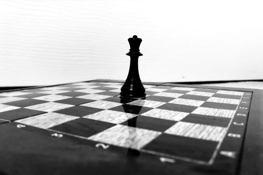 Black queen chess piece on an empty black and white chessboard.